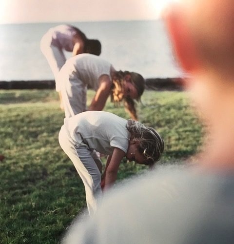 three young girls do forward bend while instructor watches